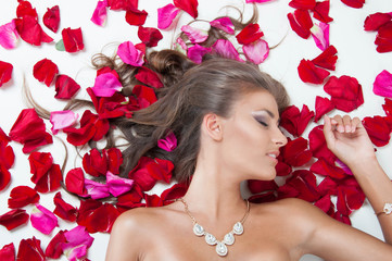 Beautiful girl lying on the petals of roses