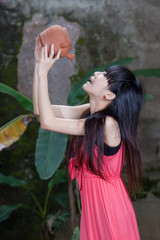 Asian girl drinking from clay pot