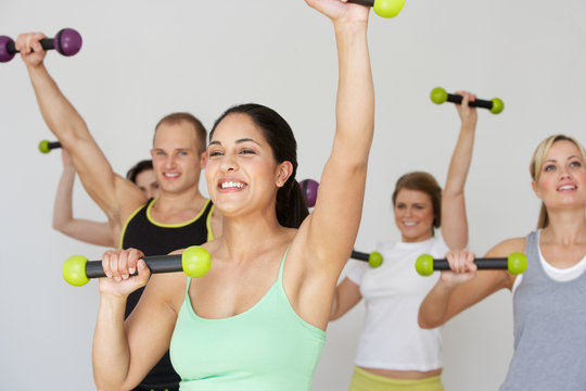 Group Of People Exercising In Dance Studio With Weights