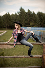 girl wearing jeans and checkered shirt sitting on the fence
