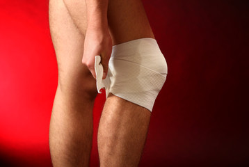 Young man with elastic bandage on knee, on red background
