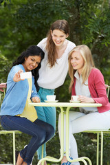 Teenage Girls Taking Photo On Mobile Phone At Outdoor cafe