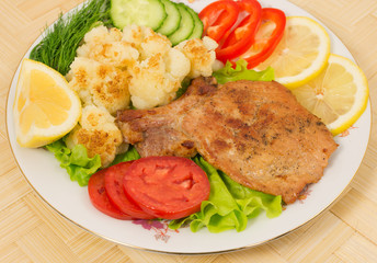 Grilled pork chop with a side dish of cauliflower and vegetables