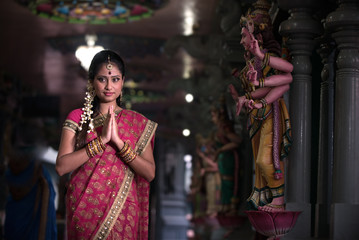 traditional Young indian woman praying in the temple