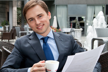 Portrait of a smiling businessman with documents