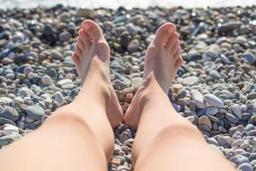 Feet girl on sea stones