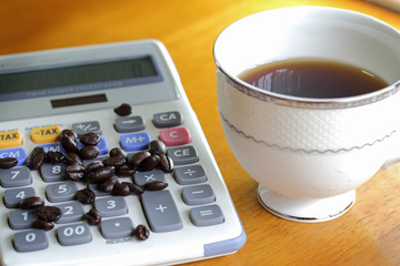 Cup of coffee and coffee beans on the calculator