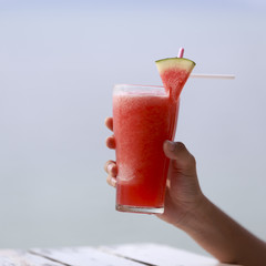 Hand hold watermelon juice with watermelon fruit