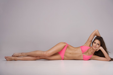 Beauty in pink bikini. Attractive young woman in bikini lying on