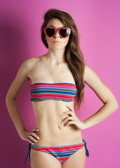 Beautiful girl with heart glasses against pink background.