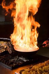 Professional cook preparing food on flame