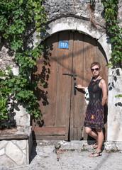 Woman in front of old wooden door