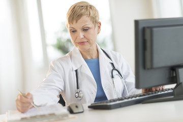 Doctor Working At Computer Desk In Clinic