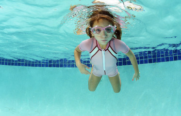 young girl holding breath underwater