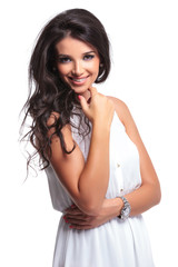 beautiful woman smiles with hand on chin