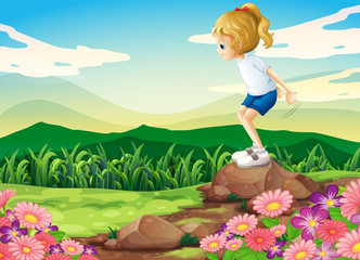 A young girl playing at the hilltop with rocks and a garden