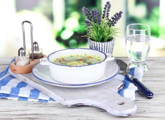 Soup in plate on napkin on wooden board on window background