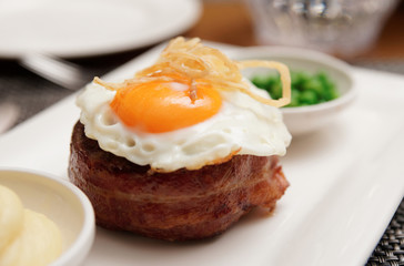 Tenderloin steak with fried egg and green pies