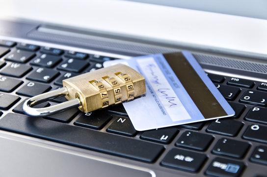 Kreditkarte/EC-Karte liegt zusammen mit einem Zahlenschloss auf einer Computertastatur