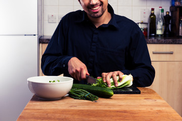 Happy man chopping lettuce in kitchen