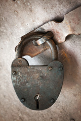 Old rusted lock hangs on metal door