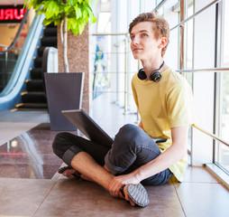 Teenager boy surf internet in modern shopping center