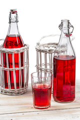 Red juice in bottles on white background
