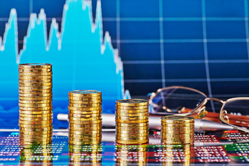 Downtrend financial chart, glasses, pen and stacks of golden coi