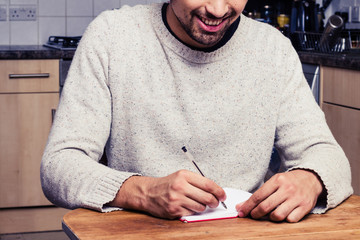 Smiling young man is writing in his kitchen