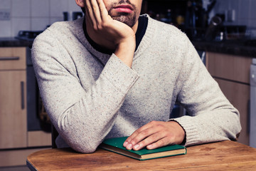 Young man with book daydreaming in kitchen