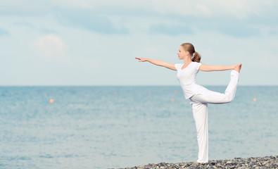 Fototapete - woman in white doing yoga on  beach