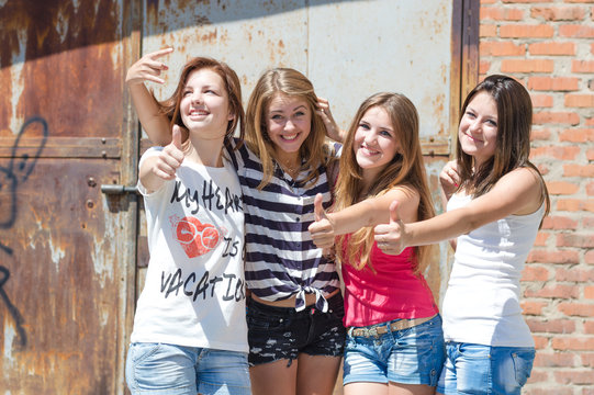 Four happy teen friends showing thumbs up outdoor