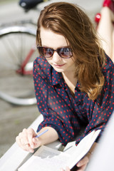 Woman lying on bench and enjoys reading
