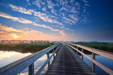 wooden bridge over river at sunrise