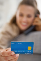 Closeup on credit card in hand of young woman talking phone
