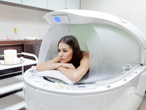 young beautiful woman at steam SPA capsule
