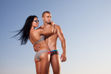 attractive fitness couple posing on sky background