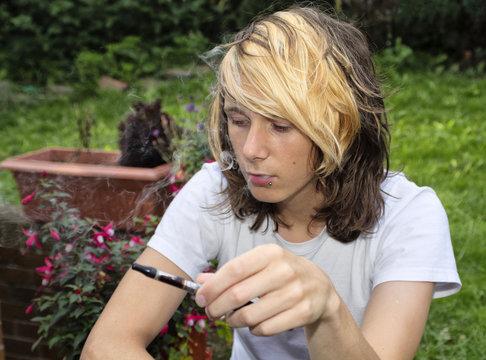 Teenage boy smoking an electronic cigarette