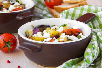 Baked stew of eggplant, zucchini, potatoes and onions with feta
