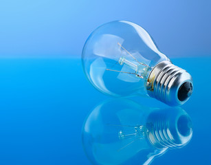 Light bulb isolated on blue glossy background