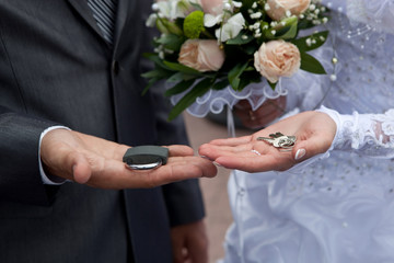 couple's hands with lock, keys, and a wedding bouquet