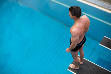 Man standing on diving board at public swimming pool