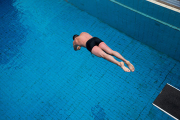 Man jumps from diving board at swimming pool