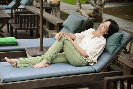 Woman resting on veranda, relaxation outdoors,