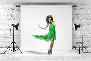 young beautiful woman in green dress posing in studio
