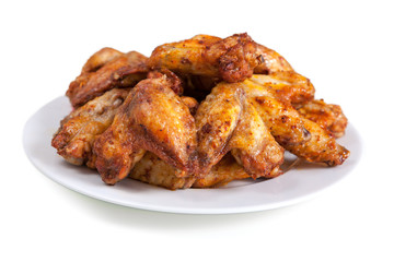 Plate of delicious barbecue chicken wings, on white