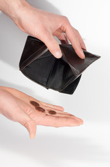 Man hands holding an empty wallet and some euro coins