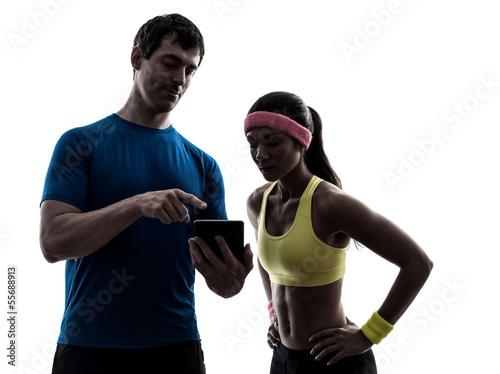 Wall mural woman exercising fitness  man coach using digital tablet