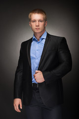 Portrait of handsome muscular  man in elegant black suit
