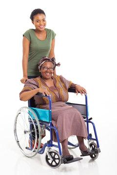 african daughter pushing senior mother on wheelchair